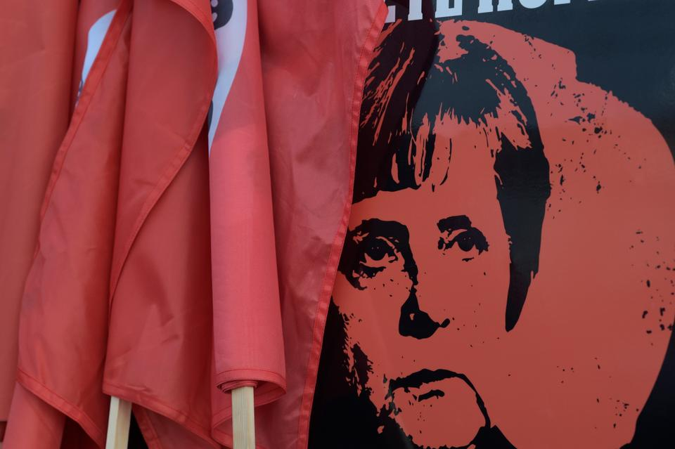 A poster showing German Chancellor Angela Merkel is displayed on a car during a protest against Merkel's visit to the German city of Chemnitz on November 16, 2018.